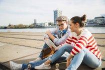 Jeune homme et femme assis sur des pistes en utilisant une tablette numérique — Photo de stock