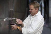 Adult caucasian winemaker testing wine from vats — Stock Photo