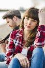 Пара, сидя на берегу реки, играя гитара — стоковое фото