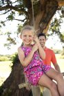 Father playing with daughter at rope swing — Stock Photo