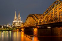 Germany, North Rhine-Westphalia, Cologne, lighted Cologne cathredral and Hohenzollern Bridge by night — Stock Photo