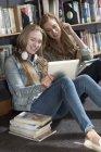 Zwei Studentinnen sitzen in Bibliothek Blick auf digital-Tablette — Stockfoto