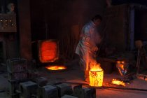 Foundry worker pouring hot metal into cast — Stock Photo