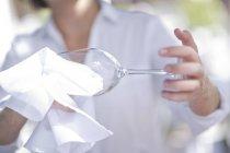 Serveuse nettoyant un verre de vin avec un chiffon — Photo de stock