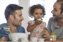 Gay couple with daughter making a cake — Stock Photo
