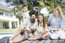 Familie am Pool mit Seifenblasen spielen — Stockfoto