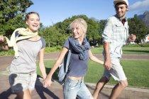 Begeisterte Freunde laufen Hand in Hand im Park — Stockfoto