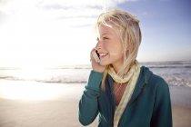 Усміхнене молоду жінку на пляжі при сходом сонця за допомогою мобільного телефону — стокове фото