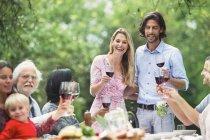Pareja sosteniendo copas de vino tinto en una fiesta de jardín - foto de stock