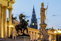 Austria, Vienna, view to parliament building, town hall tower and statue of goddess Pallas Athene by twilight — Stock Photo