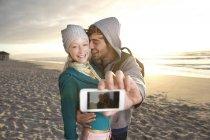 Молодая пара, принимая selfie на пляже на рассвете — стоковое фото