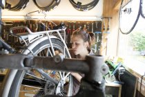 Young woman working in a bicycle repair shop — Stock Photo