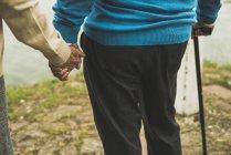 Старшие пары держатся за руки на краю воды, крупным планом — стоковое фото