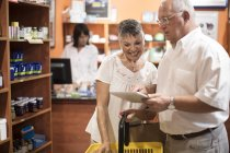 Coppie maggiori per mezzo della compressa di digital nel negozio di salute — Foto stock