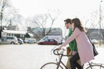 Happy couple going home together, woman riding bicycle — Stock Photo