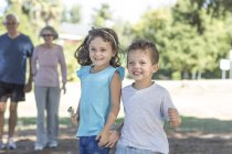 Grinning little boy and girl standing side by side — Stock Photo