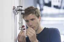 Technician adjusting lever at pipe — Stock Photo