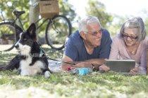 Couple de personnes âgées avec chien couché sur une couverture sur un pré à l'aide de tablette numérique — Photo de stock