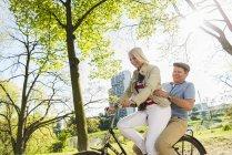 Mature couple riding bike in park, man sitting on rack — Stock Photo