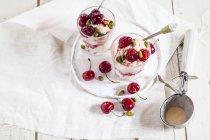 Высокий вид на стаканы ванильного мороженого с вишнями и фисташками на белом столе — стоковое фото