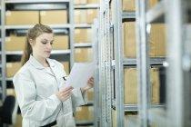 Jovem mulher no armazém olhando para o papel — Fotografia de Stock
