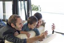 Dois homens com garoto olhando para tablet digital — Fotografia de Stock