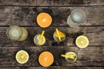 Karaffen und Gläser hausgemachte Limonade und Orangenlimonade auf dunklem Holz — Stockfoto