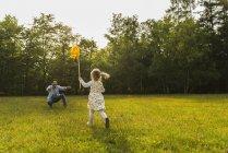Menina com moinho de vento de papel correndo para o pai no prado — Fotografia de Stock