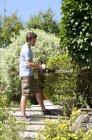Молодой человек обрезает изгородь электропилой — стоковое фото