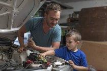 Сын, помогая отцу в дома гараж, работающих на автомобиле — стоковое фото