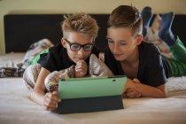 Dos chicos acostados en la cama usando tableta digital - foto de stock