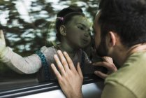 Girl kissing father behind window pane in car — Stock Photo