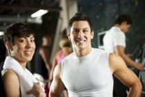 Smiling man and woman with towel looking in camera in gym — Stock Photo