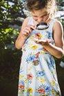 Девушка осматривает улитку с лупой — стоковое фото