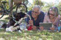 Couple de personnes âgées avec tablette numérique se trouvant sur la couverture sur une prairie — Photo de stock