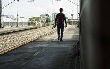 Jeune homme avec la planche à roulettes, marcher sur la plate-forme de la voie ferrée — Photo de stock