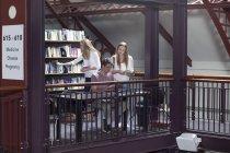 Молодые кавказские студенты вместе в библиотеке — стоковое фото