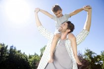 Father carrying son on shoulders — Stock Photo