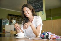 Portrait of smiling woman with cup of cappucino in a cafe — Stock Photo