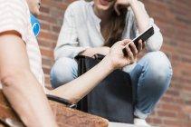 Junger Mann mit Handy, Frau — Stockfoto