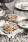 Rhubarb tartelettes with almonds and tea on rustic wooden table — Stock Photo