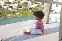Дівчинка з Кучеряве волосся, сидячи на терасі — стокове фото