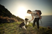 Man with dog at the coast at sunset — Stock Photo