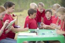 Niños y mujeres explorando la naturaleza con equipo científico - foto de stock