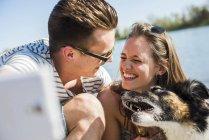 Счастливая молодая пара принимая selfie с собакой на берегу реки — стоковое фото