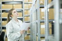 Jovem mulher no armazém olhando para cima — Fotografia de Stock