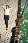 Relaxed mature woman lying on deck of a sailing ship — Stock Photo