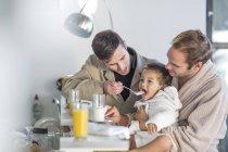 Coppia gay alimentazione colazione figlio — Foto stock