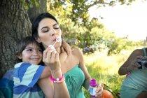 Madre con figlio all'albero che soffia bolle di sapone — Foto stock