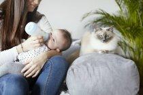 Молодая мать кормит ребенка бутылкой с котом на диване — стоковое фото